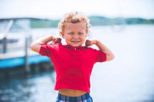 criança fazendo gesto de confiança em si mesmo pose de super-herói