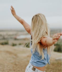Mulher demonstra confiança em si mesma com braços apertos para o ar