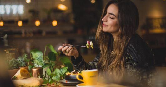 Mulher se alimenta e sorri, nutrição amorosa